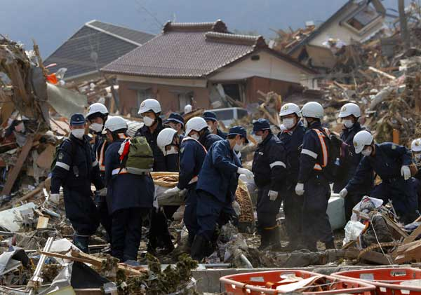 Police officers carry the body of a victim in Rikuzentakata, Iwate Prefecture, northern Japan, Monday, March 14, 2011, three days after northeastern coastal towns were devastated by an earthquake and tsunami.  <span class=meta>(&#40;AP Photo&#47;Itsuo Inouye&#41; )</span>